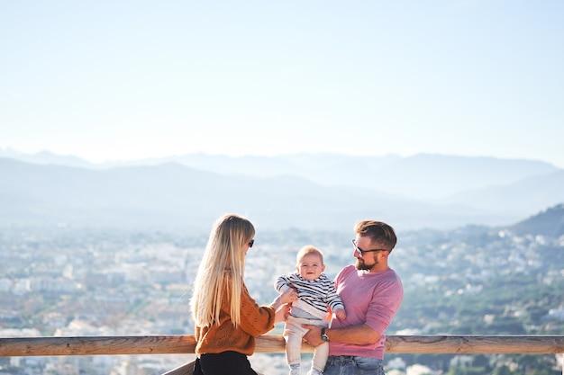 Giovane famiglia felice con il piccolo ragazzo sveglio che gode del giorno soleggiato