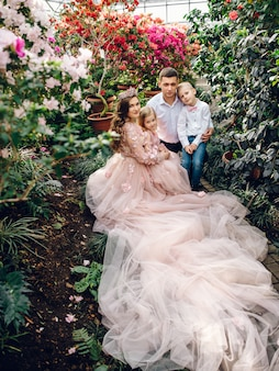 Giovane famiglia felice in un giardino fiorito di primavera