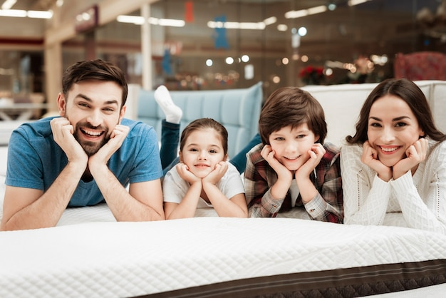 Giovane famiglia felice rilassante sul letto morbido nel negozio
