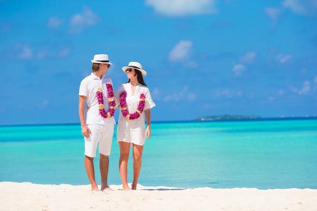 Giovane famiglia felice sulla spiaggia bianca alle vacanze estive