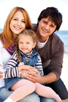 Giovane famiglia in spiaggia in autunno.