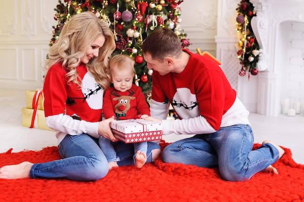Giovane famiglia-mamma, papà e figlio piccolo in albero di natale. i genitori fanno un regalo di natale al loro bambino.