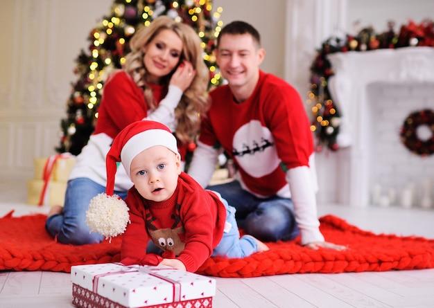 Giovane famiglia-mamma, papà e figlio piccolo in albero di natale. un bambino con il cappello rosso di babbo natale gattona per un regalo di natale.