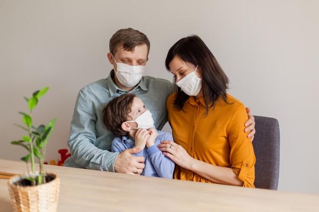 Giovane famiglia moderna coronavirus in quarantena in maschere mediche. la chiamata a rimanere a casa ferma la pandemia. l'autoisolamento insieme è la soluzione. care covid-19. mamma papà figlio millennials