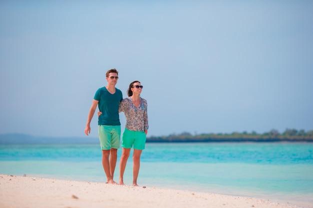 Giovane famiglia sulla spiaggia bianca durante le vacanze estive. gli amanti felici si godono la luna di miele sull'isola esotica