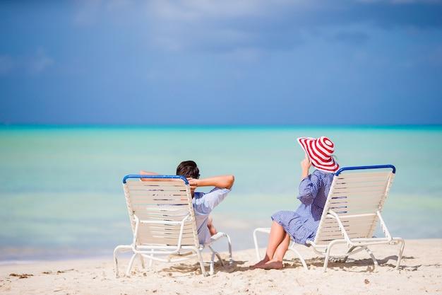 Giovane famiglia sulla spiaggia bianca durante le vacanze estive.