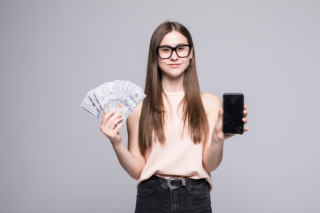 Giovane fan americano emozionante della tenuta della donna delle banconote in dollari e del telefono cellulare d'argento isolato sopra la parete bianca