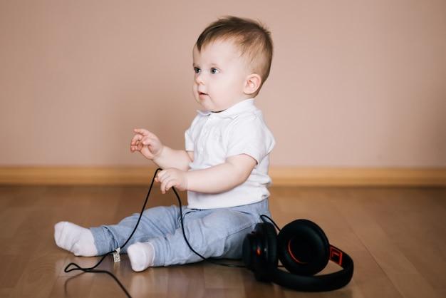 Giovane fare da baby-sitter sveglio sul pavimento a casa che gioca con le cuffie che ascolta la musica