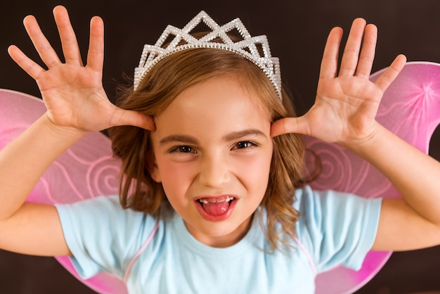 Giovane fata con ali rosa e corona bianca in testa.