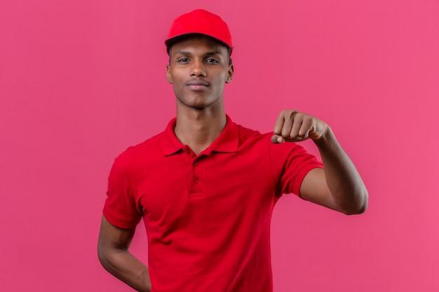 Giovane fattorino afroamericano che indossa la camicia e il cappuccio di polo rossi che stanno con l'innalzamento del concetto del vincitore del pugno sopra il rosa isolato