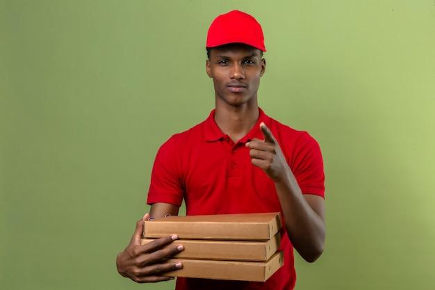 Giovane fattorino afroamericano che indossa la camicia e il cappuccio di polo rossi che stanno con la pila di scatole della pizza che indicano dito la macchina fotografica sopra verde isolato