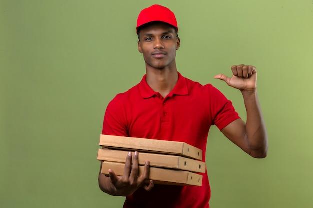 Giovane fattorino afroamericano che indossa la camicia e il cappuccio di polo rossi che stanno con la pila di scatole di pizza che indicano dito se stesso esaminando sicuro isolato verde