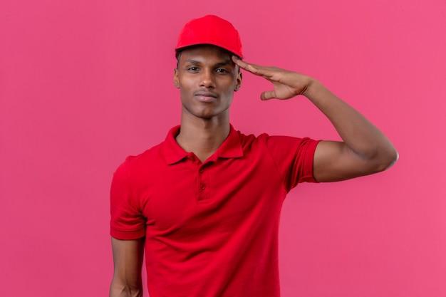 Giovane fattorino afroamericano che indossa la camicia e il cappuccio di polo rossi con il fronte serio che saluta sopra il rosa isolato