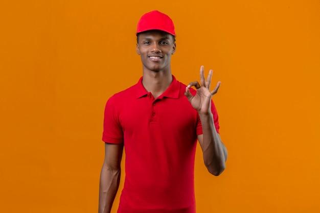 Giovane fattorino afroamericano che indossa la camicia e il cappuccio di polo rossi con il sorriso sul fronte che fa segno giusto con le dita sopra l'arancia isolata