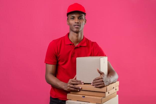 Giovane fattorino afroamericano che indossa la camicia e il cappuccio di polo rossi con la pila di scatole che esaminano macchina fotografica sopra il rosa isolato
