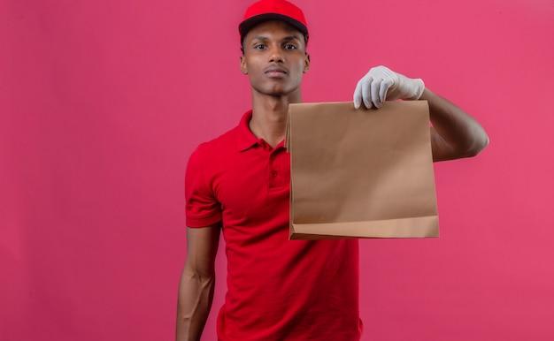 Giovane fattorino afroamericano che indossa la camicia e il cappuccio di polo rossi in guanti protettivi che tengono sacco di carta con alimento asportabile sopra il rosa isolato