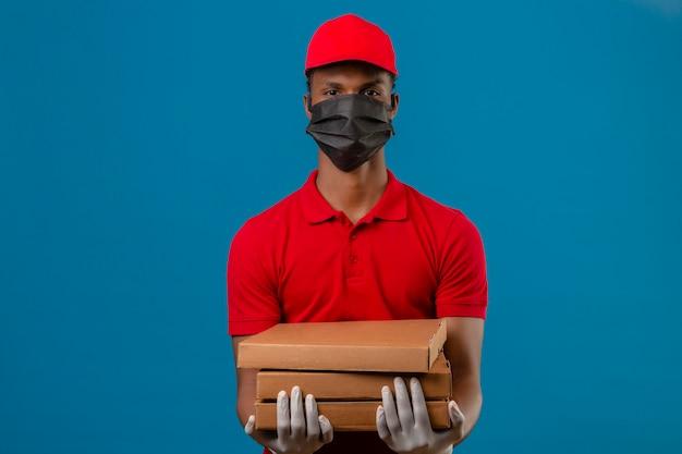 Giovane fattorino afroamericano che indossa la camicia e il cappuccio di polo rossi in maschera protettiva e guanti che stanno con la pila di scatole della pizza con il fronte serio sopra il blu isolato