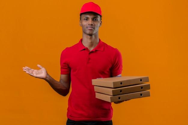 Giovane fattorino afroamericano che indossa la pila della tenuta della camicia e del cappuccio di polo rosso di scatole della pizza che sembrano sconcertanti e che hanno dubbi sopra l'arancia isolata