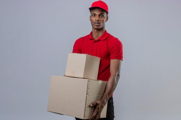 Giovane fattorino afroamericano che indossa la pila della tenuta della camicia e del cappuccio di polo rosso di scatole di cartone che esaminano macchina fotografica con il fronte serio sopra bianco isolato