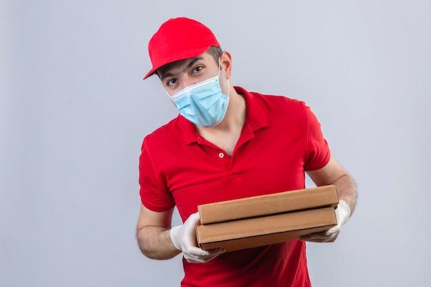 Giovane fattorino in camicia e cappuccio di polo rossi in scatole mediche della pizza della tenuta della maschera che esaminano interrogativamente la macchina fotografica che controlla parete bianca isolata