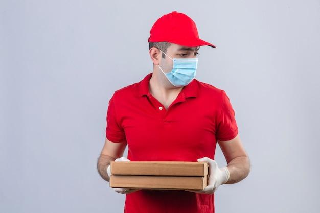 Giovane fattorino in camicia e cappuccio di polo rossi in scatole mediche della pizza della tenuta della maschera che guardano al lato con interesse sopra la parete bianca isolata