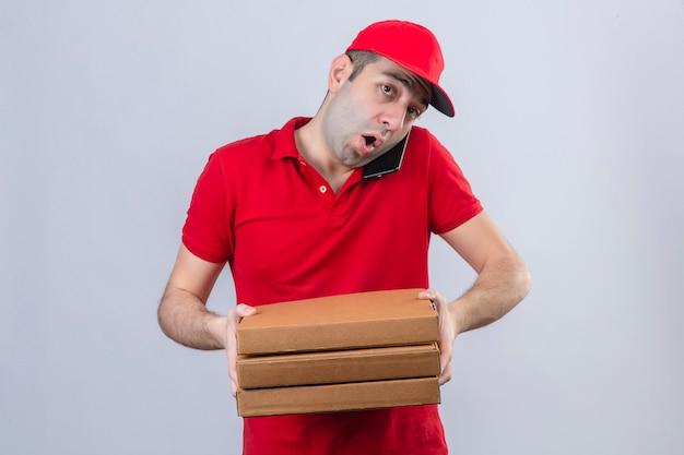 Giovane fattorino in scatole della pizza della tenuta della camicia e del cappuccio di polo rosso mentre parlando sul telefono cellulare che sembra sorpreso sopra la parete bianca isolata