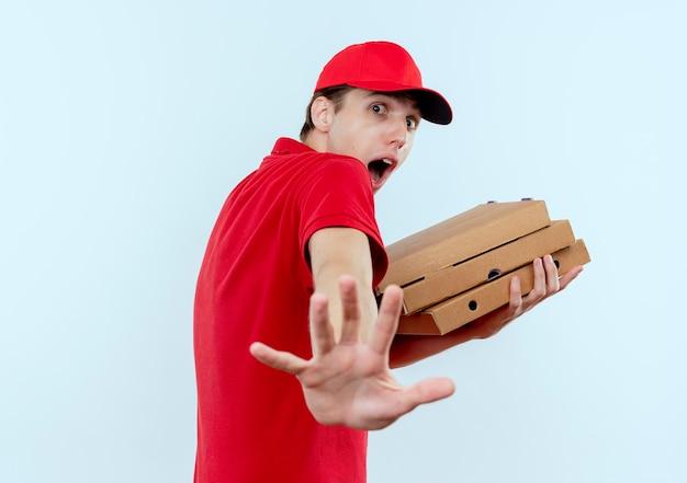 Giovane fattorino in uniforme rossa e cappuccio che tiene le scatole per pizza molto spaventato facendo il gesto di difesa con la mano in piedi sul muro bianco