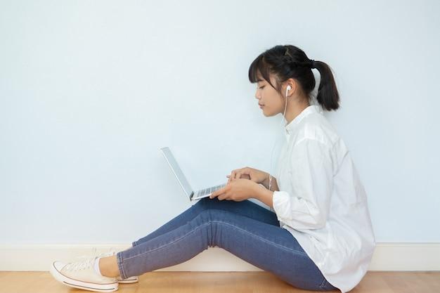 Giovane felice bella asiatica studiando, seduto sul pavimento per la formazione apprendimento online studio