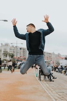 Giovane felice che salta nell'aria con le mani in su