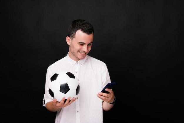 Giovane felice che tiene una palla di calcio o di calcio che guarda la partita online sul suo smart phone su fondo nero.