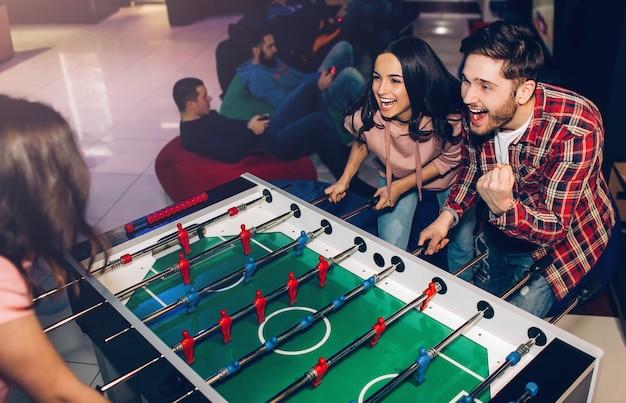 Giovane felice e donna che giocano insieme nella sala. gioco intenso. vincere e perdere. avversari al calcio balilla.
