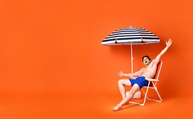 Giovane felice senza camicia che si siede sulla sedia di spiaggia che sorride con le armi stese
