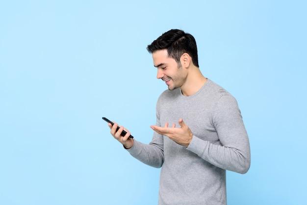 Giovane felice sorridente che per mezzo dello smartphone isolato
