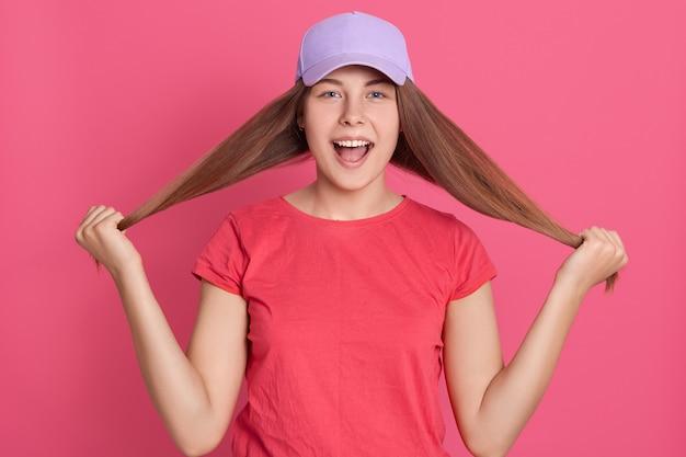 Giovane femmina adorabile positiva che tira i suoi capelli diritti lunghi con la mano sollevata e che guarda allegramente, isolata sopra la parete rosa.