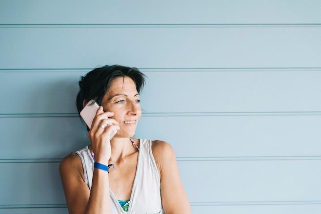 Giovane femmina adulta in abito estivo a parlare al cellulare mentre appoggiato a parete con pannelli in legno