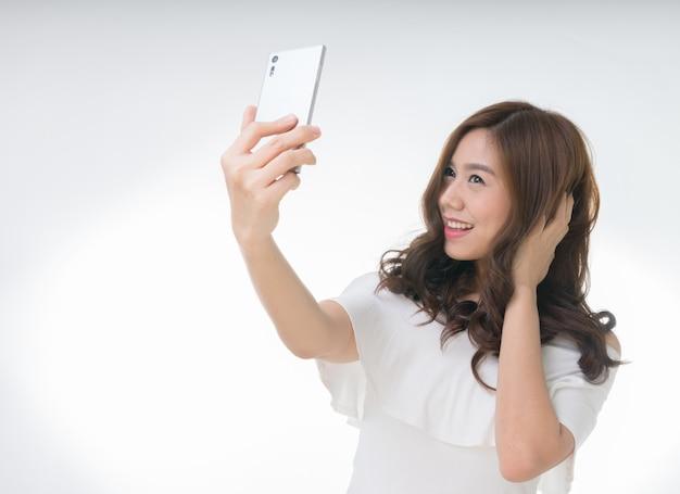 Giovane femmina asiatica attraente che prende selfie, su bianco