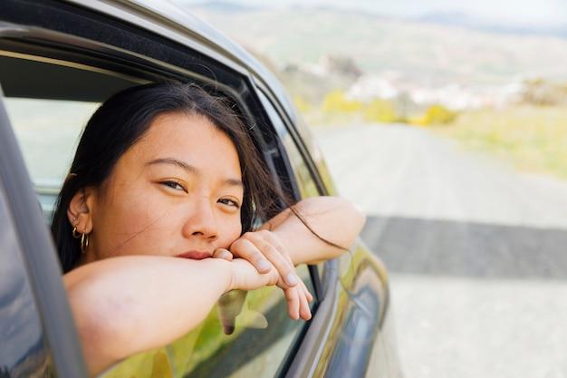 Giovane femmina asiatica che osserva fuori la finestra della macchina