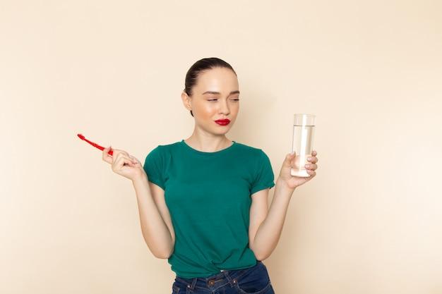 Giovane femmina attraente di vista frontale in camicia verde scuro che tiene spazzolino da denti e acqua sul beige