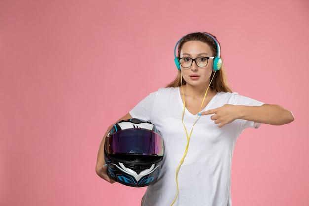Giovane femmina attraente di vista frontale in cappotto colorato della maglietta bianca che ascolta il casco della tenuta di musica sui precedenti rosa