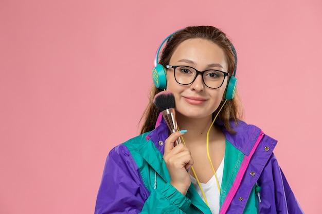 Giovane femmina attraente di vista frontale in cappotto colorato della maglietta bianca che ascolta la musica con le cuffie sui precedenti rosa