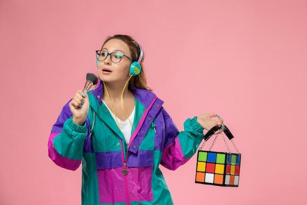 Giovane femmina attraente di vista frontale in cappotto colorato della maglietta bianca che ascolta la musica sui precedenti dentellare