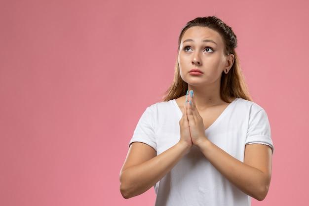 Giovane femmina attraente di vista frontale in maglietta bianca che posa e che prega sui precedenti rosa