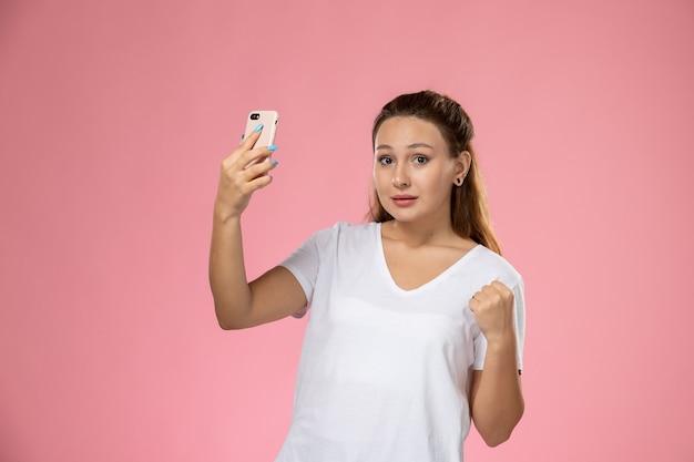 Giovane femmina attraente di vista frontale in maglietta bianca che prende un selfie su fondo rosa