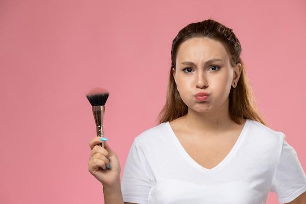 Giovane femmina attraente di vista frontale in maglietta bianca che tiene il pennello per il trucco su sfondo rosa