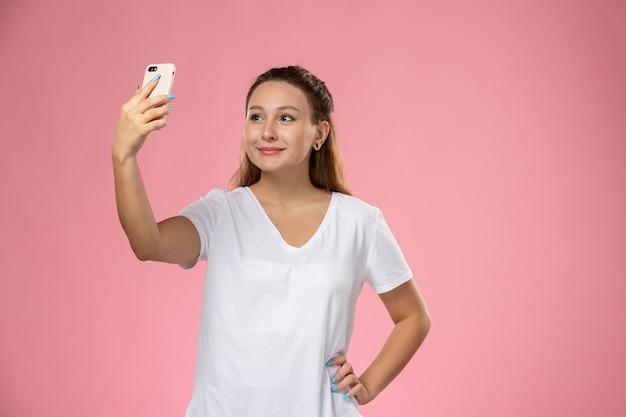 Giovane femmina attraente di vista frontale in maglietta bianca con il sorriso che prende un selfie sui precedenti rosa