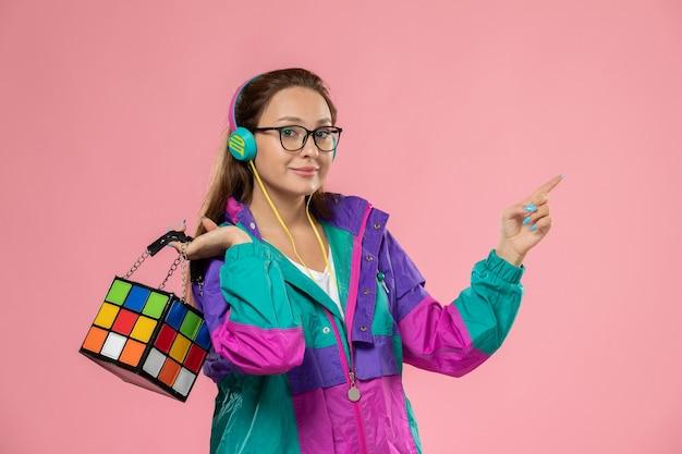 Giovane femmina attraente di vista frontale in maglietta bianca e cappotto colorato che ascolta la musica con gli auricolari sui precedenti rosa