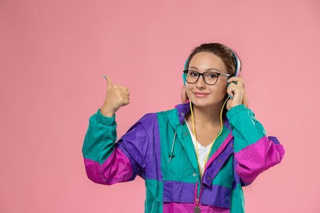 Giovane femmina attraente di vista frontale in maglietta bianca e cappotto colorato che ascolta la musica e che sorride sui precedenti rosa