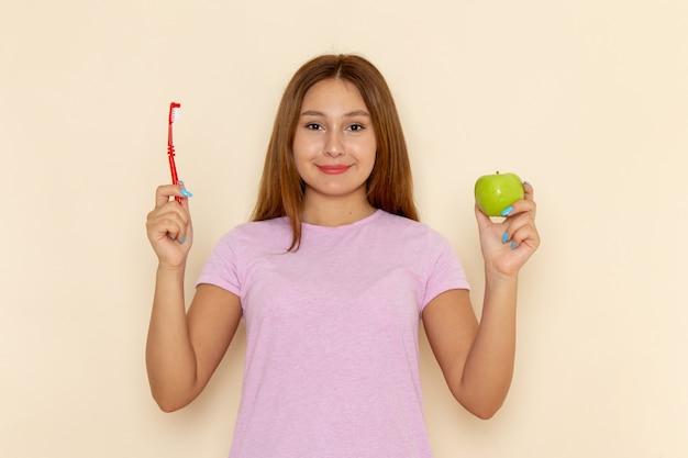 Giovane femmina attraente di vista frontale in maglietta rosa e blue jeans che tengono mela e spazzolino da denti