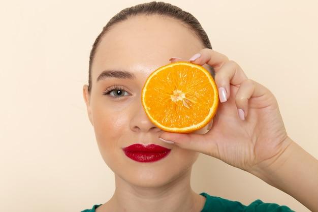 Giovane femmina attraente di vista vicina della parte anteriore in camicia verde scuro che tiene mezza arancia