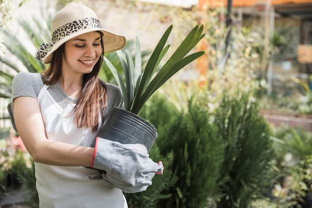 Giovane femmina attraente sorridente ad una scuola materna del fiore che tiene una pianta in vaso
